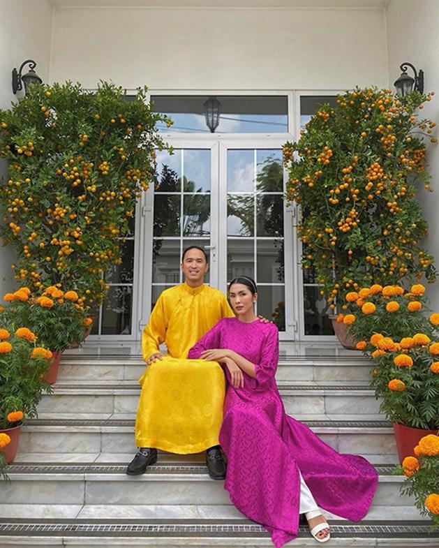 """Vợ chồng """"ngọc nữ"""" Tăng Thanh Hà diện áo dài sắc màu, trưng hoa trái vàng rực lối đi và vườn cây để chào mừng năm mới."""