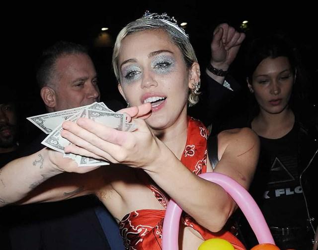 """Bị bắt ra khỏi hộp đêm, Miley Cyrus đã đánh lạc hướng các tay săn ảnh bằng cách """"tắm"""" cho họ bằng tiền mặt."""
