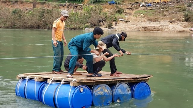 Người dân làng Tắc Rối vượt sông Tranh bằng bè.