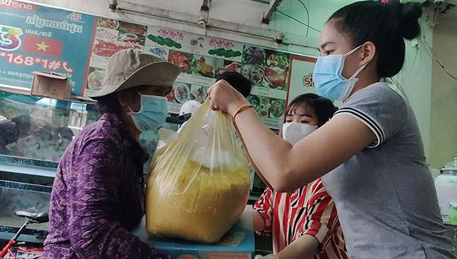 Bà con gốc Việt tại Phnom Penh nhận quà cứu trợ. Nguồn: Nhandan.vn.
