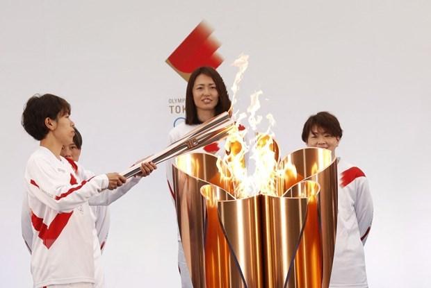Vận động viên bóng đá Nhật Bản Azusa Iwashimizu (trái) thắp sáng ngọn đuốc Olympic tại lễ rước đuốc Olympic Tokyo 2020, ở Naraha, tỉnh Fukushima, Nhật Bản, ngày 25/3/2021. Ảnh: AFP/TTXVN.