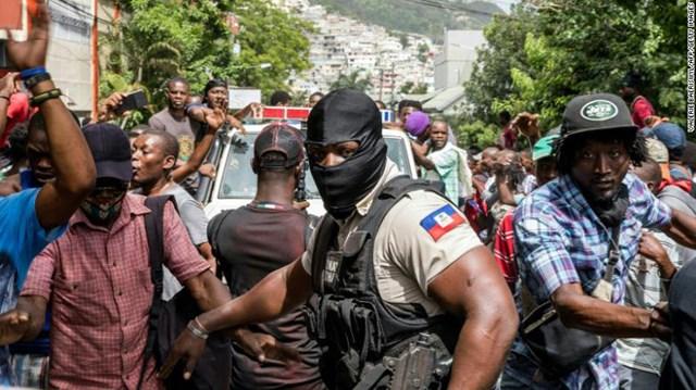 Người dân vây quanh xe cảnh sát chở các nghi phạm. Ảnh: Reuters.