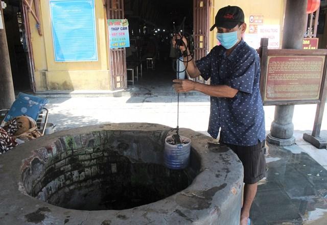 Ông Lê Văn Bê lấy nước từ giếng Máy.