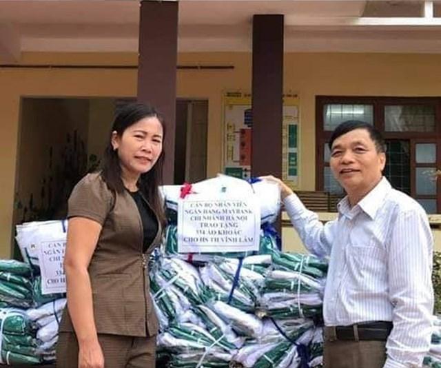 Hiệu trưởng trường Tiểu học Vĩnh Lâm tiếp nhận quà, đồ cứu trợ cho học sinh trường Vĩnh Lâm.