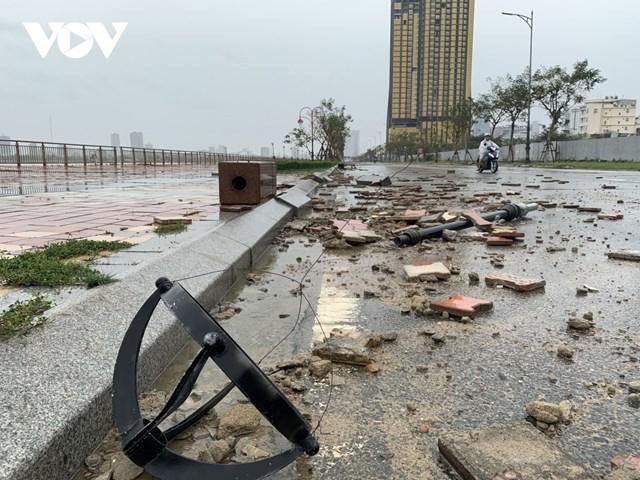 Hệ thống trụ điện ghế đá cũ bị giật đổ, đất đá vương vãi trên đường.