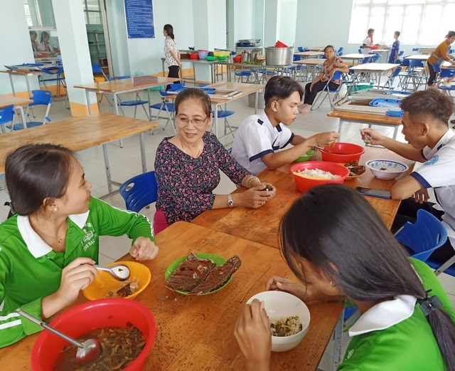 Cô Kim Dung cùng trò chuyện, thăm hỏi các em học sinh nội trú bữa ăn ở nhà ăn sau giờ học.
