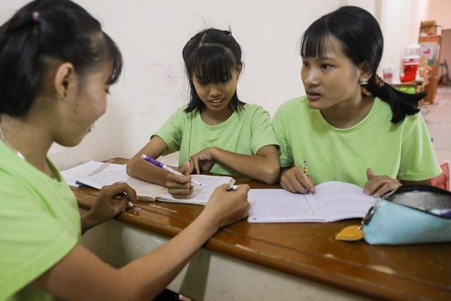 Ba chị em Yến Nhi (16 tuổi, góc phải) chăm chú trao đổi sau khi được giao bài tập. Cả ba chị em đều học hành dang dở, đang theo học chương trình lớp 5, ban ngày đi phụ bán quán phở. Ngoài ra, em trai của Nhi cũng đang học lớp 3 tại đây.