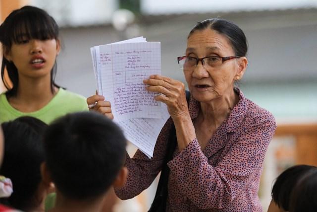 """Sau phần điểm danh, bà giáo về hưu nhận xét từng bài kiểm tra của học trò. """"Từng bài tôi đều có lời phê kỹ càng và nhận xét cụ thể. Em nào làm bài tốt, thể hiện sự tiến bộ tôi đều đề nghị cả lớp vỗ tay động viên"""", bà Ba nói."""