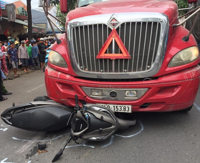 Chiếc xe máy dính chặt vào đầu xe container, bị đẩy đi 1 đoạn trên đường.