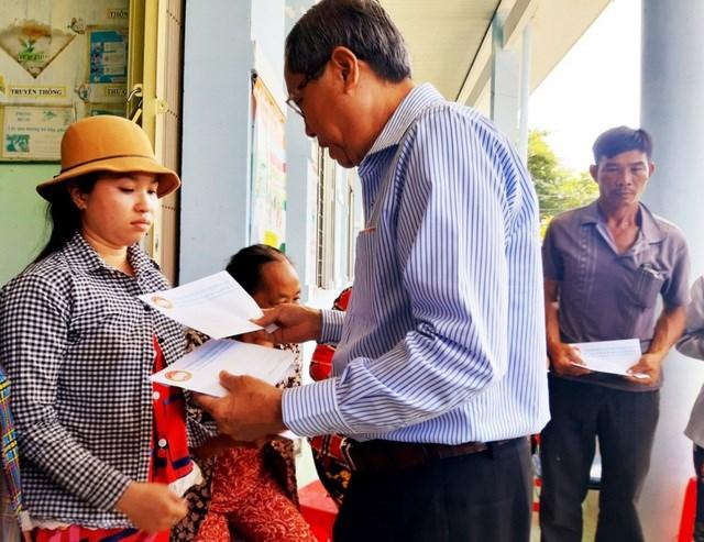 Phó Bí thư Thường trực Tỉnh ủy An Giang Lê Văn Nưng trao tiền hỗ trợ cho các hộ bị thiệt hại do hỏa hoạn.