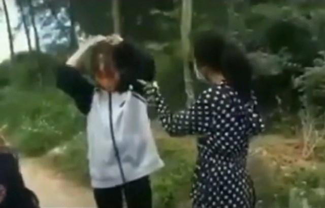 Hình ảnh nữ sinh dùng mũ bảo hiểm đánh bạn (Ảnh cắt từ clip).
