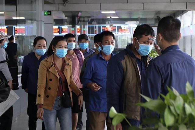 Đo thân nhiệt cho hành khách tại bến xe Nước Ngầm (Hà Nội).