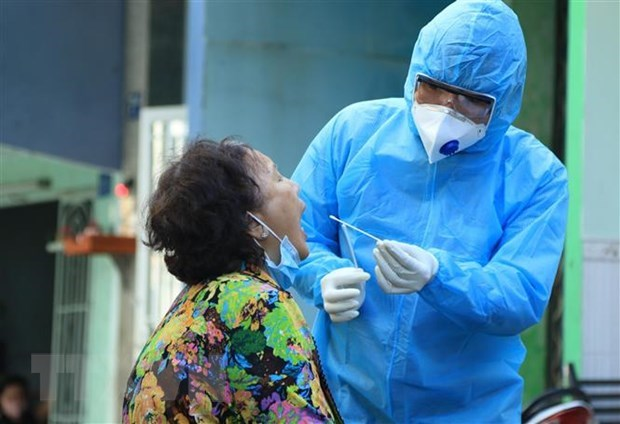 Nhân viên y tế lấy mẫu xét nghiệm người dân trong khu vực Lô E, Lò Gốm (phường 7, quận 6, TP HCM). Ảnh: TTXVN.