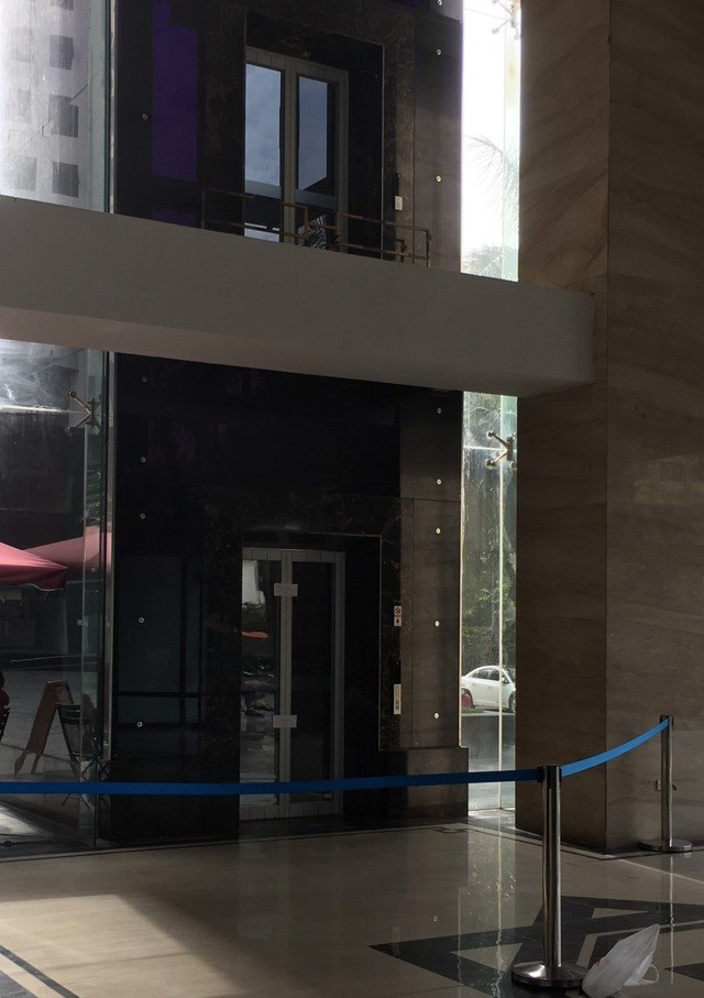 Hiện cửa thang đã được đặt barie ngăn không cho ai sử dụng. Dưới tầng 1 nơi người đàn ông ngã xuống cũng đã được căng dây chắn lại. Ảnh: Dân Trí.