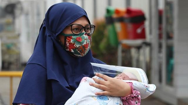 Một bà mẹ Indonesia lo ngại cho đứa con của mình trong dịch Covid-19.