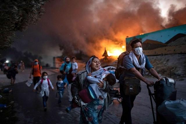 Những người di cư chạy trốn khỏi đám cháy tại trại tị nạn Moria trên đảo Lesbos, Hy Lạp ngày 9/9. Vụ hỏa hoạn đã thiêu rụi trại tị nạn lớn nhất châu Âu, khiến khoảng 12.000 người không có nơi trú ẩn. Ảnh: AP.