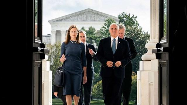 Thẩm phán Amy Coney Barrett và Phó Tổng thống Mike Pence bước lên các bậc thang của Điện Capitol để gặp các thượng nghị sĩ ở Washington vào ngày 29/9. Ông Trump đề cử bà Amy Coney Barrett thay thế cho cố thẩm phán Ruth Bader Ginsburg. Ảnh: Reuters.