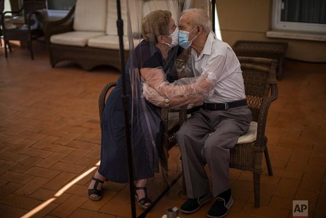 Agustina Canamero, 81 tuổi và Pascual Perez, 84 tuổi, trao nhau nụ hôn qua tấm chắn nhựa tại một viện dưỡng lão ở Barcelona (Tây Ban Nha) để phòng dịch Covid-19. Ảnh: AP.