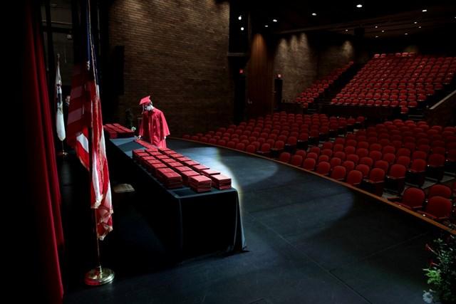 Một học sinh nhận bằng tốt nghiệp tại Trường Trung học Cộng đồng Bradley-Bourbonnais trong một khán phòng trống rỗng, không có bạn bè, gia đình hoặc người thân nào được tham dự do đại dịch Covid-19. Ảnh: Getty Images.