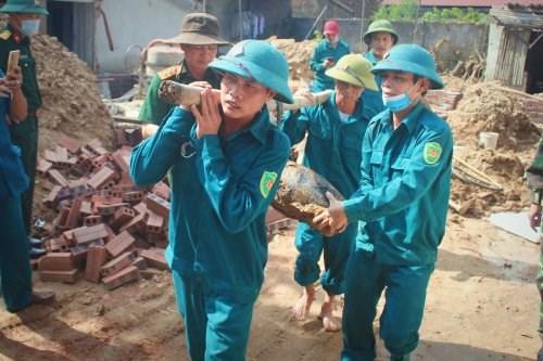 Lực lượng dân quân tự vệ di dời bom ra khỏi khu vực nhà dân.