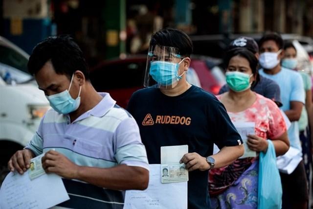 Người dân xếp hàng chờ xét nghiệm Covid-19 tại một chợ hải sản ở Samut Sakhon, Thái Lan. Ảnh: AFP.