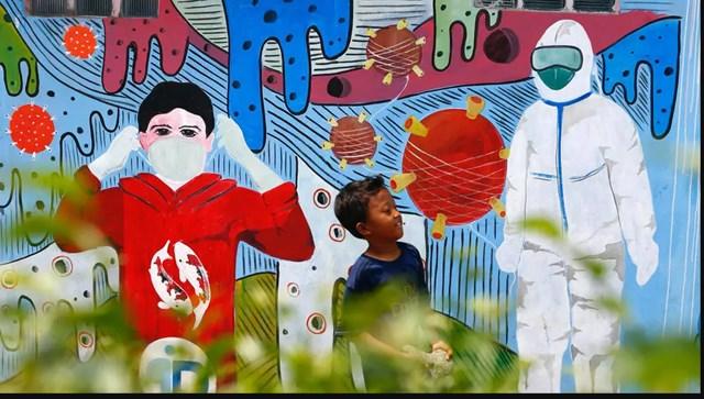 Một bức tường với hình cổ động phòng chống dịch Covid-19, ở Depok, ngoại ô Jakarta, Indonesia Ảnh: REUTERS.
