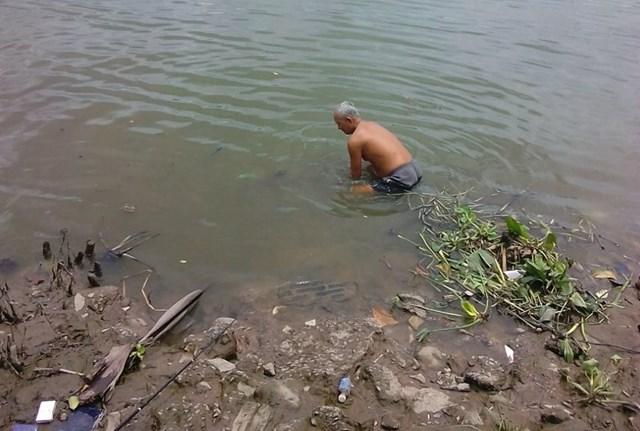 Nhiều năm qua, ông Kính trầm mình dưới nước để nhặt rác, khơi thông dòng chảy. (Ảnh nhân vật cung cấp).
