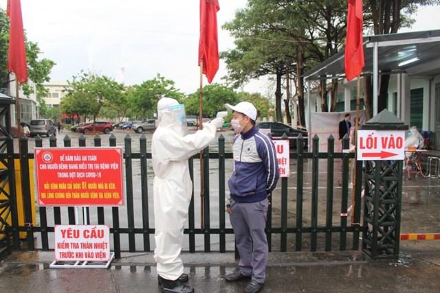 Nhân viên Bệnh viện Đa khoa khu vực Cẩm Phả đo thân nhiệt cho người dân đến khám, chữa bệnh. Ảnh: Báo Quảng Ninh.