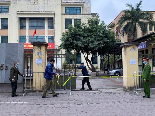 Lực lượng chức năng phong tỏa Văn phòng công chứng số 3tại số 6 phố Duy Tân nơi ca nhiễm Covid-19 mới đến làm hợp đồng mua nhà. Ảnh: Lan Anh.