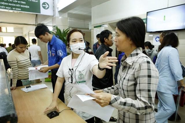 Nhân viên công tác xã hội hướng dẫn người bệnh làm thủ tục khám chữa bệnh tại Bệnh viện Bạch Mai. Ảnh: Dương Ngọc.