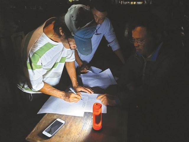 Các thành viên Ban Công tác Mặt trận và Trưởng thôn Vinh Quang, xã Sơn Thủy, huyện Lệ Thủy, tỉnh Quảng Bình lên danh sách các hộ dân bị thiệt hại do lũ ngay trong đêm. Ảnh: Q.Nghĩa.