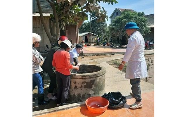 Cán bộ Trung tâm Y tế huyện Minh Hóa (Quảng Bình) hướng dẫn người dân xử lý nguồn nước sạch sau ngập lụt Ảnh: Hương GIang.