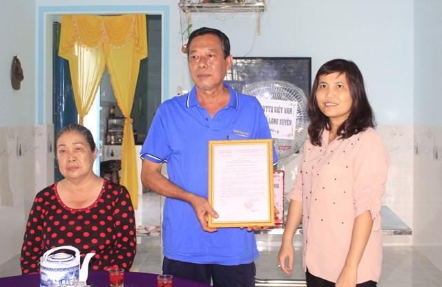 Cán bộ Mặt trận An Giang trao quyết định tặng nhà cho hộ gia đình khó khăn. Ảnh: Nguyễn Hưng.
