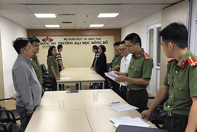 Cơ quan Công an tống đạt quyết định khởi tố bị can tại Trường Đại học Đông Đô. Ảnh: PLO.