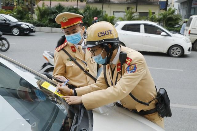 Đội Cảnh sát giao thông số 7 tiến hành dán thông báo xử phạt nguội lên kính xe. Ảnh: Quang Vinh.