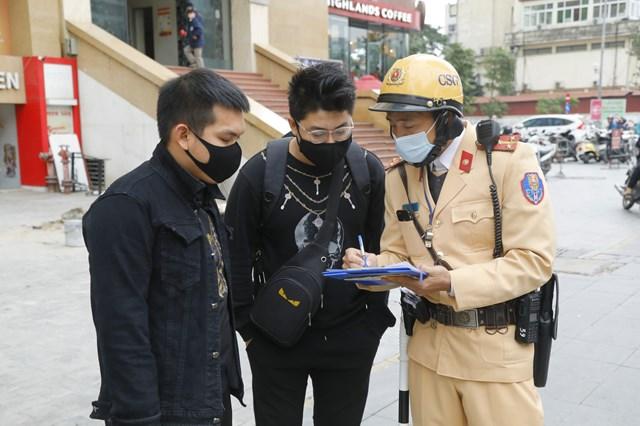 Cảnh sát giao thông lấy ý kiến của người làm chứng trong khi dán thông báo phạt nguội lên phương tiện dừng, đỗ sai quy định.Ảnh:Quang Vinh.