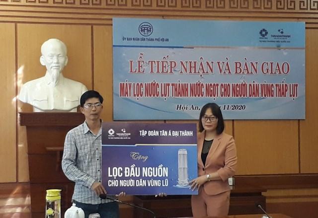 Đại diện tập đoàn Tân Á Đại trao tặng máy lọc nước đầu nguồn cho người dân vùng lũ