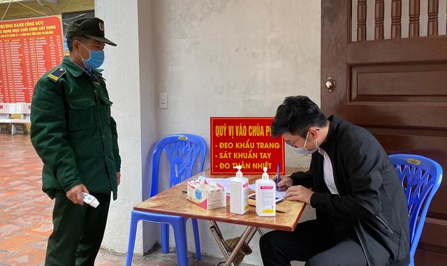 Người dân thực hiện nghiêm túc việc đeo khẩu trang, sát khuẩn tay và đo thân nhiệt trước khi vào chùa Long Tiên (TP Hạ Long, Quảng Ninh).