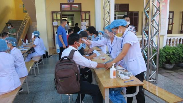 Các nhân viên y tế thực hiện khám sàng lọc sức khỏe cho người dân trước khi tiêm Vaccine.