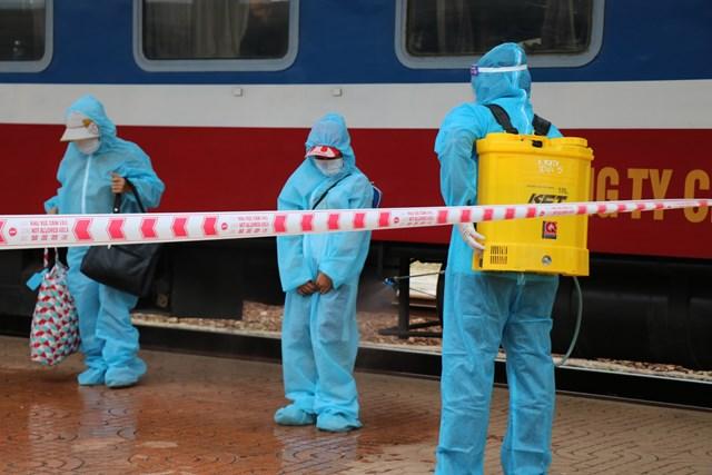 Người dân xuống tàu lần lượt, được lực lượng y tế phun khử khuẩn người và hành lý ngay tại lối đi.