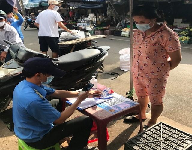 """Tiểu thương đang thực hiện quét mã QR qua hình thức """"Thẻ kiểm soát dịch bệnh"""" tại chợ Đông Ba, TP Huế. Ảnh: Xuân Sơn."""