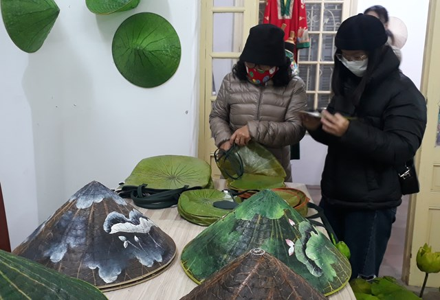 Du khách tham quan các sản phẩm như túi đựng và nón lá được làm từ lá sen.