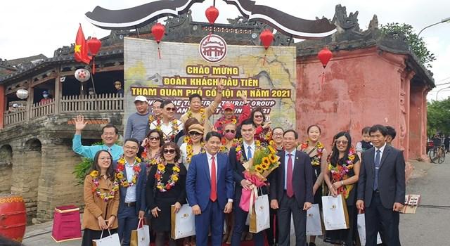 Đoàn khách đầu tiên đến tham quan phố cổ Hội An chụp ảnh lưu niệm.