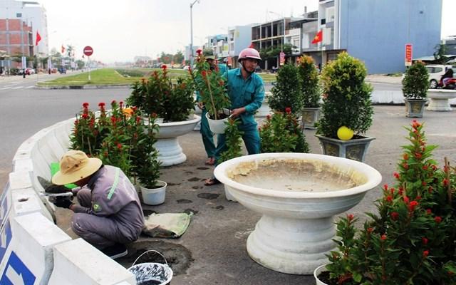 Các công nhân đang chỉnh sửa, trang trí vòng xuyến ở TP Tam Kỳ.