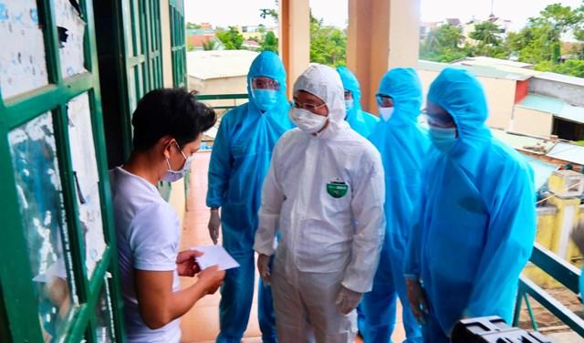 Ông Lê Trí Thanh (bảo hộ trắng) thăm hỏi công dân từ TP HCM về cách ly ở TP Tam Kỳ.