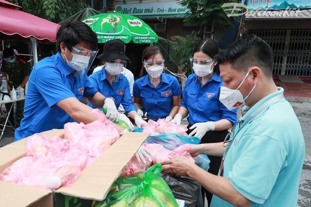 Chi đoàn báo Đại Đoàn Kết tham gia hỗ trợ suất cơm cho người nghèo (Ảnh: Quang Vinh).