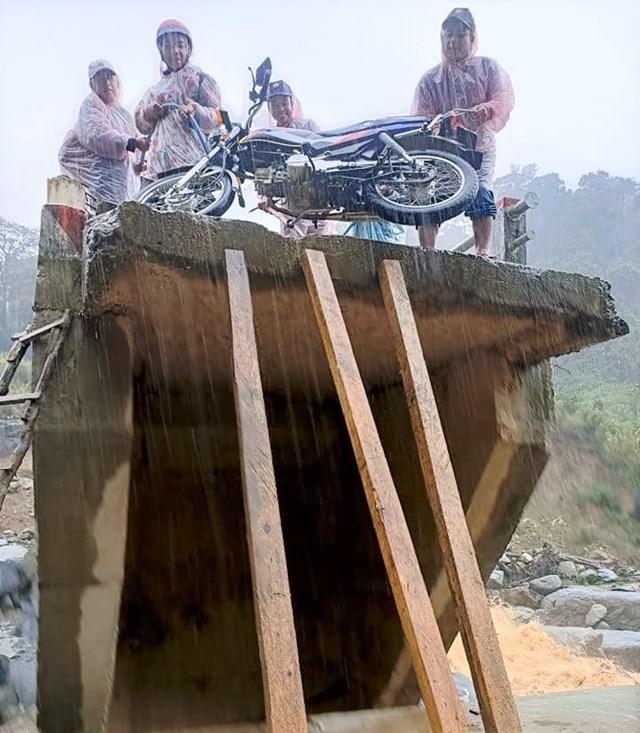Người dân đưa xe qua đoạn cây cầu hư hỏng ở xã Phước Lộc.