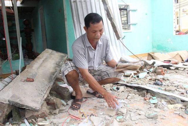 Ông Liệp nhặt những giấy tờ còn sót lại trong ngôi nhà.