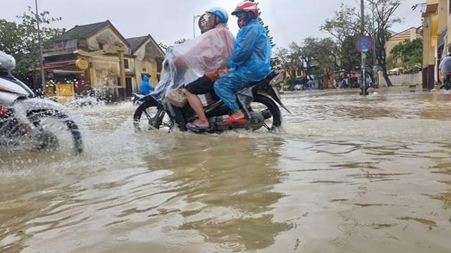 Người dân dùng xe máy đi qua những đoạn ít ngập nước.