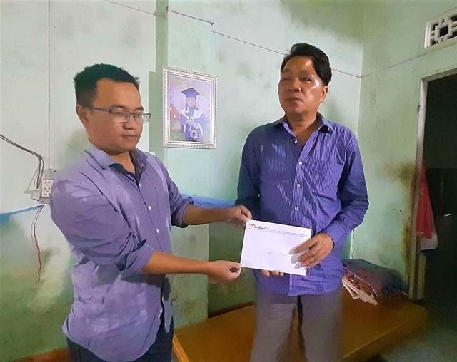 Đại diện VP báo Đại Đoàn Kết (bên trái) trao tiền hỗ trợ của bạn đọc cho ông Bùi Đình An.